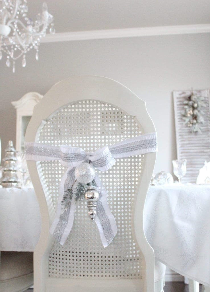 adding glam to christmas decor winter wonderland tablescape bows on chairs