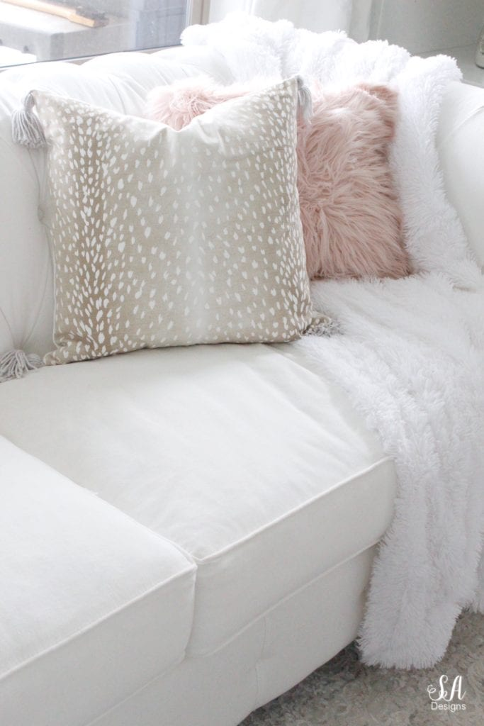 loveliest looks of fall tour, beige taupe fawn print pillow cover tassels, blush faux fur pillow, white tufted chesterfield sofa nailhead trim, white faux fur throw blanket