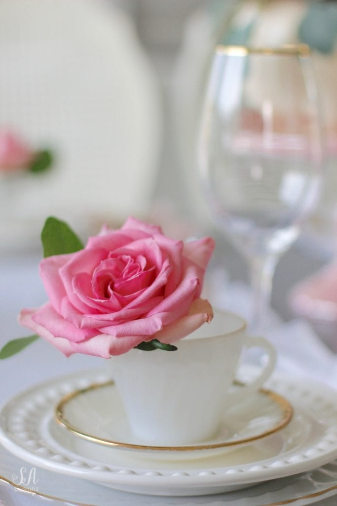 milk glass teacup, fresh pink roses, crystal chandelier, crystorama chandelier, white faux pumpkin floral arrangement, romantic floral brunch tablescape, girls table, brunch table, girlfriends party, fall party, fall tablescape, blush pink ruffle dinner linen napkins, white ruffle table runners, gold flatware, white beaded pottery barn dishes, white beaded world market dishes, gold rimmed goblets wine glasses, pink tablescape, pink table decor, place settings, vintage milk glass dinnerware