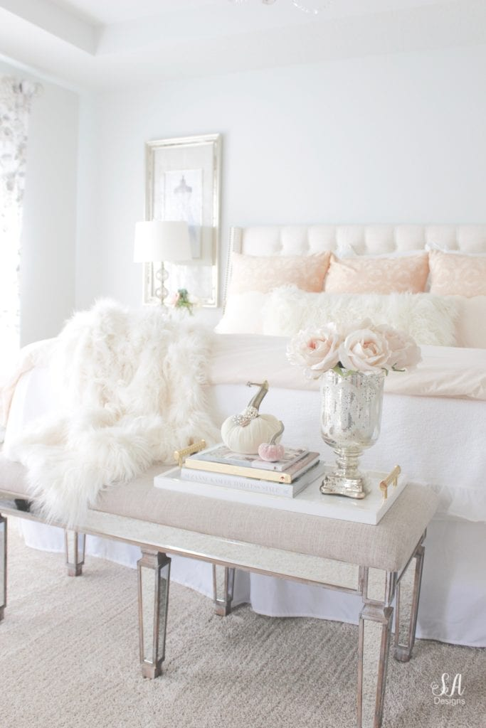 blush pink bedding, pom pom at home, romantic homes, romantic feminine bedroom, faux fur throw blanket, faux fur lumbar oblong pillow, tufted headboard skyline furniture, mirrored bench, chandelier, winter bedding, fall bedding, velvet pumpkins, hotskwash pumpkins, french provincial dresser, french style inspired vanity, agape candles, pink matches, pumpkin candle, fall candle