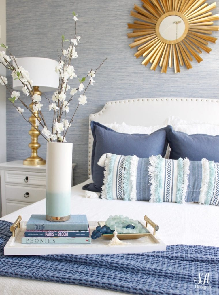 blue and white decor, guest bedroom design, gold brass accents, sunburst mirror, blue faux grasscloth wallpaper, white headboard, decorating with books, gold lamps