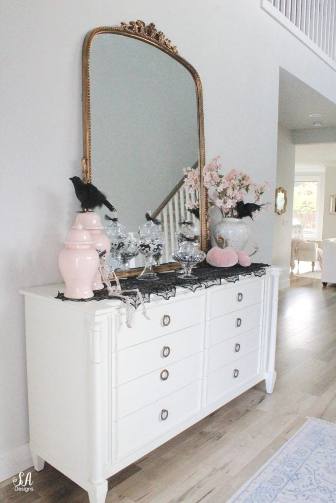 anthropologie primrose mirror, white interiors, entry decor, entry design, 2 story entry, halloween decor, black and white halloween decor decorations, pink halloween, chic halloween, glam halloween, elegant halloween, blush pink halloween decor, velvet pumpkins, pink temple jars, pink ginger jars, blush ginger jars, spider web table runner tablecloth, crystal shell oyster ginger jar, cherry blossom stems, black ravens crows, apothecary jars with candy, faux fur white settee lucite acrylic legs, blush pink ruffle throw blanket, black and white leopard pillow, west elm gold brass marble side table, georgianna lane books, black grey leopard print velvet hot skwash pumpkins, georgianna lane book dahlias vintage roses, Lo Home