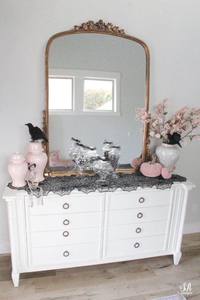 anthropologie primrose mirror, white interiors, entry decor, entry design, 2 story entry, halloween decor, black and white halloween decor decorations, pink halloween, chic halloween, glam halloween, elegant halloween, blush pink halloween decor, velvet pumpkins, pink temple jars, pink ginger jars, blush ginger jars, spider web table runner tablecloth, crystal shell oyster ginger jar, cherry blossom stems, black ravens crows, apothecary jars with candy