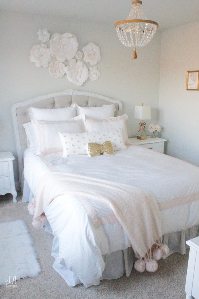 blush bedroom, blush and gold, blush gold grey, modern vintage style, modern vintage bedroom, modern vintage home decor, paper flowers on wall, french provincial furniture nightstands, gold hardware, pottery barn teen pottery barn kids monique lhuillier ethereal sateen duvet shams bedding, pbteen, sparkly crystal chandelier, pbkids chandelier, blush pink satin windows curtains window treatments, vintage gold bow mirror, kate spade ellery ivory bow lamps gold finish, nordstrom at home blush pink pom pom throw blanket, restoration hardware children and baby colette bed, grey tufted modern vintage headboard, white vanity, faux fur vanity stool, girls vanity, girls bedroom ideas, tween teen girls bedroom