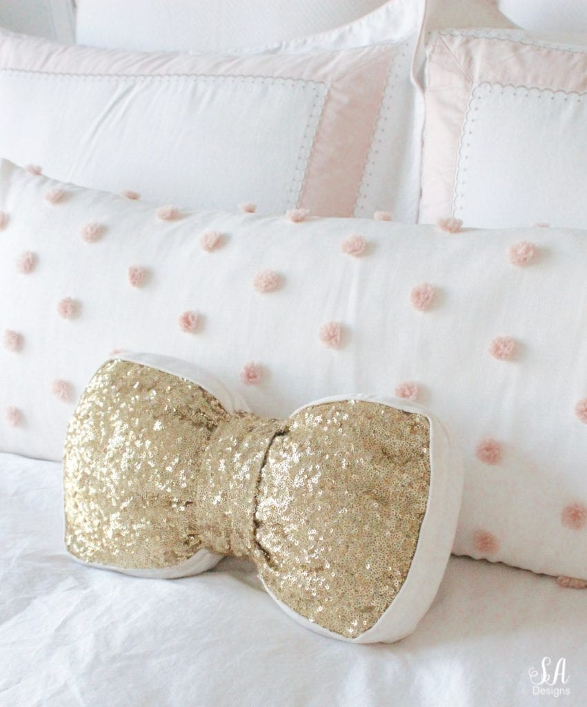 emily & meritt gold sequin bow pillow, blush bedroom, blush and gold, blush gold grey, modern vintage style, modern vintage bedroom, modern vintage home decor, paper flowers on wall, french provincial furniture nightstands, gold hardware, pottery barn teen pottery barn kids monique lhuillier ethereal sateen duvet shams bedding, pbteen, sparkly crystal chandelier, pbkids chandelier, blush pink satin windows curtains window treatments, vintage gold bow mirror, kate spade ellery ivory bow lamps gold finish, nordstrom at home blush pink pom pom throw blanket, restoration hardware children and baby colette bed, grey tufted modern vintage headboard, white vanity, faux fur vanity stool, girls vanity, girls bedroom ideas, tween teen girls bedroom