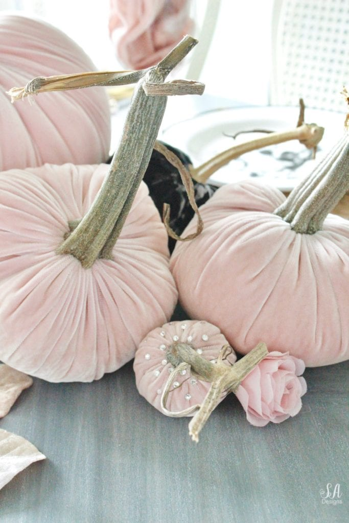 hotskwash velvet pumpkins, pink fall decor, blush fall decor, decorating with pumpkins, glam Halloween tablescape, elegant halloween decor, white halloween kitchen with pink and black, pink halloween, skull halloween plates homegoods, pier1 blush velvet placemats charger, gold rimmed clear crystal goblets, gold flatware, crystal chandelier, velvet pumpkins with swarovski crystals