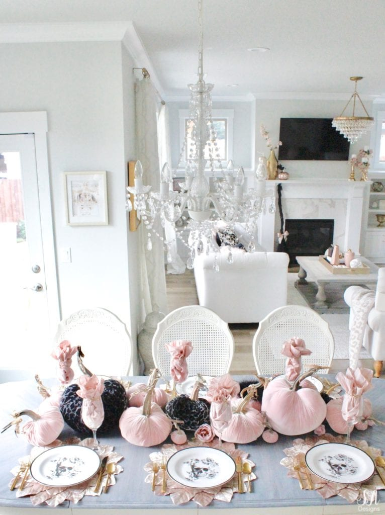 hotskwash velvet pumpkins, pink fall decor, blush fall decor, decorating with pumpkins, glam Halloween tablescape, elegant halloween decor, white halloween kitchen with pink and black, pink halloween, skull halloween plates homegoods, pier1 blush velvet placemats charger, gold rimmed clear crystal goblets, gold flatware, crystal chandelier