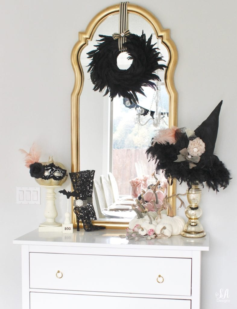 halloween living room, glam chic classy elegant halloween decor, glam halloween mantel, pink and black halloween decor, white interiors, black white gold leopard print embroidered pillow covers CB2, blush mohair faux fur throw pillows, white tufted chesterfield sofas, pier1 blush vases, glam candles, halloween mantel decor, bling skull, gold tray, brass crystal chandelier, tv over mantel, tv above mantel mantle, halloween buffet