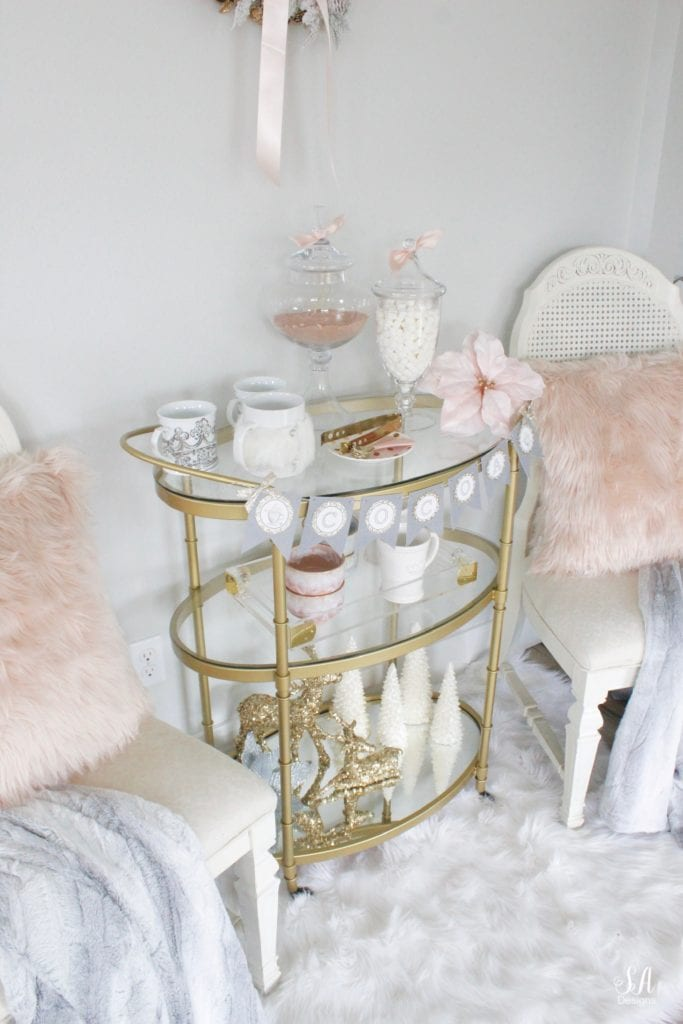 faux fur white rug, faux fur dusty blue throw blankets, blush peach pink faux fur throw pillows, vintage dining chairs white, brass gold bar cart 3 tier, diy hot cocoa station bar cart banner garland, glitter sequin white faux deer head, deer wall decoration, flocked white wreath, gold opalhouse brass wreath, blush and blue christmas, apothecary jars for hot chocolate, gold sequin glitter deer, white glitter christmas tree candles, pier one faux fur mug, acrylic brass tray, anthropologie home blue and pink bowls, white crown mugs, deer head with rhinestone crown, deer with blush satin bow