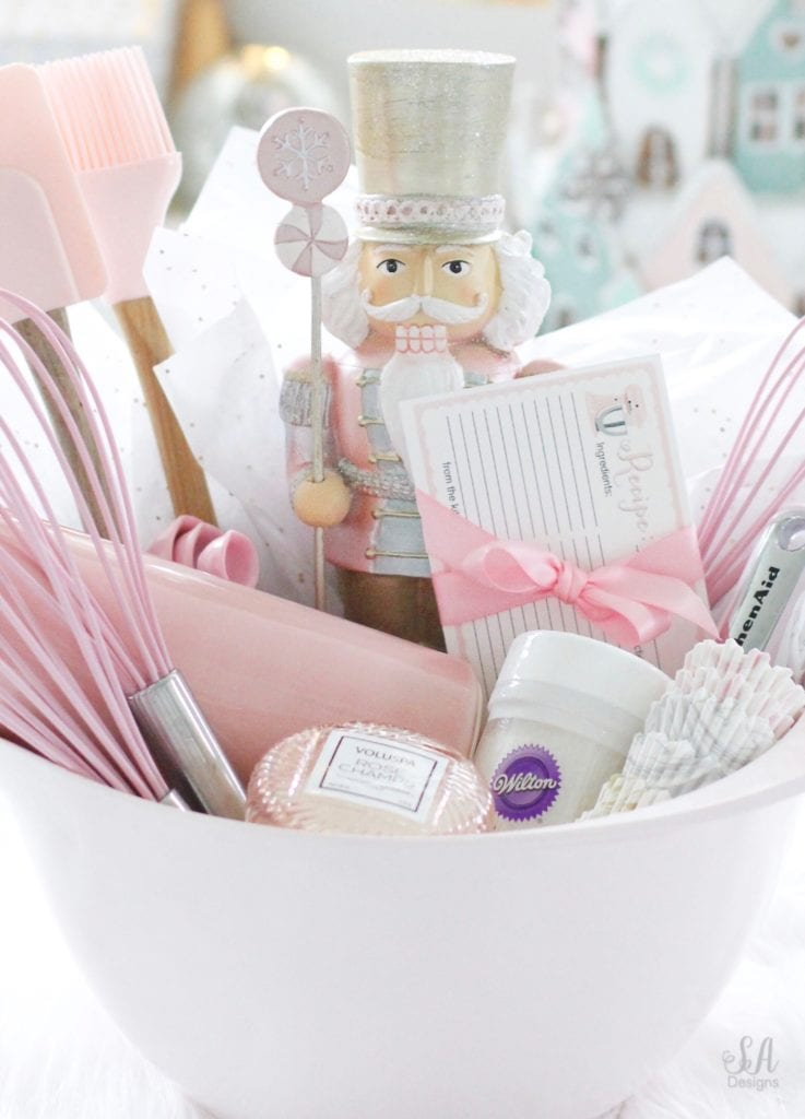 pink gift basket, kitchen utensil gift basket, diy gift ideas, pink christmas, pink kitchenaid, pink mixing bowls, pink kitchen utensils, diy recipe cards, pink recipe cards, pink nutcracker, pink rolling pin, pink whisk, pink measuring spoons, pink macaron candle, voluspa candle, gift ideas for her