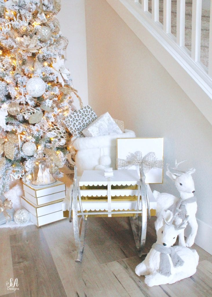 12 foot slim flocked christmas tree king of christmas, mixed metals christmas decor ornaments, whitel gold silver champagne christmas decor, glam christmas decor, elegant christmas decor, christmas sleigh, gift wrapping, presents underneath tree, white faux deer christmas figurines pier1, flocked garland