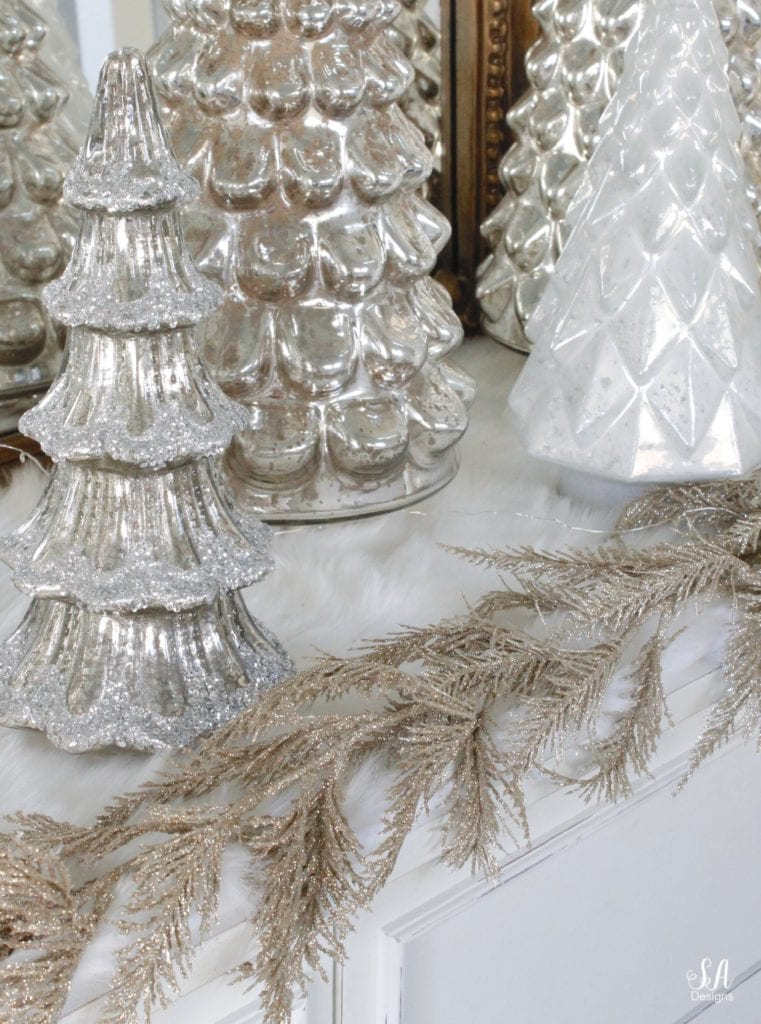 gold champagne glitter leaves garland Joanns fabrics, pottery barn mercury glass trees, anthropologie gleaming primrose glass mirror, elegant mixed metal decor, gold wreath, perigold dresser entry buffet table white transitional style buffet, michaels white faux fur christmas trees