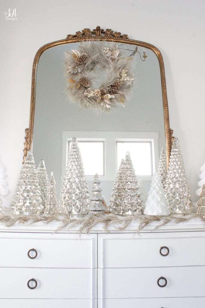gold champagne christmas wreath gold leaves, pottery barn mercury glass trees, anthropologie gleaming primrose glass mirror, elegant mixed metal decor, gold wreath, perigold dresser entry buffet table white transitional style buffet, michaels white faux fur christmas trees