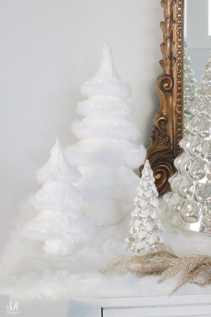 pottery barn mercury glass trees, anthropologie gleaming primrose glass mirror, elegant mixed metal decor, gold wreath, perigold dresser entry buffet table white transitional style buffet, michaels white faux fur christmas trees