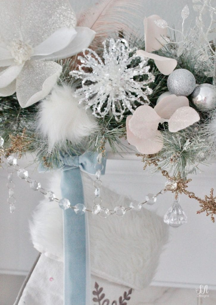 dreamy whimsical fantasy playful christmas mantel, faux fur stockings with snowflakes, christmas flocked garland with jewel rhinestone gold glitter pearl jewels garland, blush feather, faux fur pom poms, white glitter berry christmas stems, sparkly glitter christmas magnolia stems, dusty blue velvet ribbon, glitter snowflakes, joann fabric white swan figures, mercury glass candlesticks, cozy glam winter wonderland christmas, white fireplace marble tile