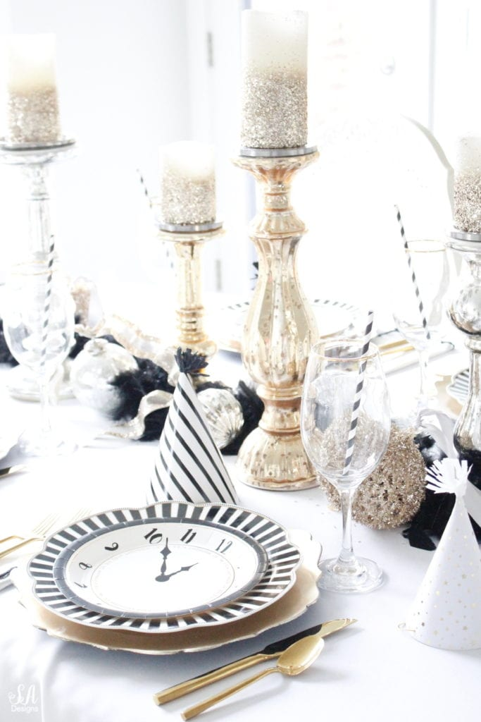 black white gold tablescape, black and white striped graces dinner plates, gold chargers, crystal chandelier, clock plates new years eve, new years eve game, new years eve food, mercury glass candlesticks, sugar paper la white black scalloped dinner napkins, party hat, mercury glass candlesticks, glitter candles. gold rimmed crystal goblets red wine glasses, gold silver ornaments, mercury glass ornaments with ribbon