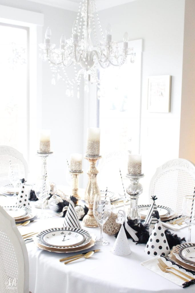 black white gold tablescape, black and white striped graces dinner plates, gold chargers, crystal chandelier, clock plates new years eve, new years eve game, new years eve food, mercury glass candlesticks, sugar paper la white black scalloped dinner napkins, party hat, mercury glass candlesticks, glitter candles. gold rimmed crystal goblets red wine glasses