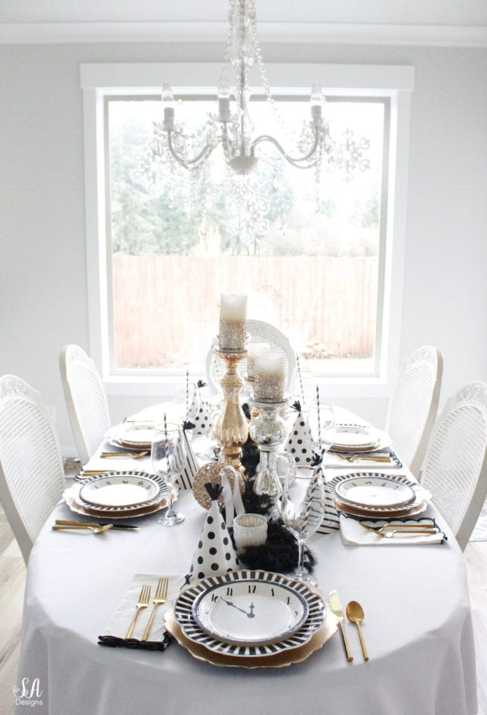 black white gold tablescape, black and white striped graces dinner plates, gold chargers, crystal chandelier, clock plates new years eve, new years eve game, new years eve food, mercury glass candlesticks, sugar paper la white black scalloped dinner napkins, party hat, mercury glass candlesticks, glitter candles
