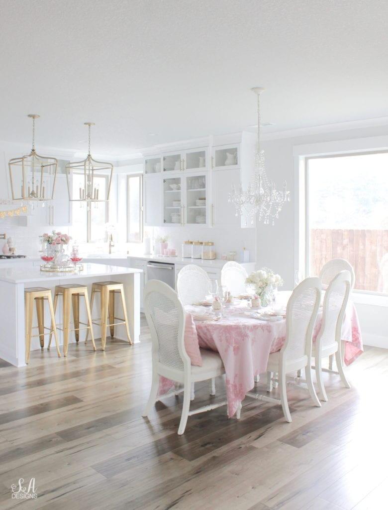 monique lhuillier pottery barn, pink floral tablecloth, pink floral plates, white kitchen design, vintage valentines day tablescape, valentines decor table