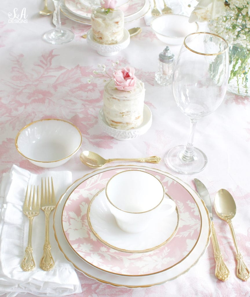 monique lhuillier pottery barn, pink floral tablecloth, pink floral plates, white kitchen design, vintage valentines day tablescape, valentines decor table, antique vintage milk glass plates teacups saucers gold rimmed, gold rimmed crystal goblets, vintage gold flatware, white ruffled napkins, individual mini naked cakes with fresh pink rose baby's breath