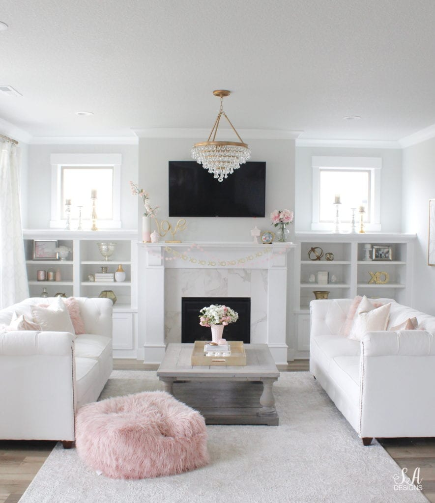 blush pink valentine's day decor, crystorama chandelier, white and gold interiors, white interiors, classy interiors, television above mantel mantle, tv above fireplace, valentines banner garland, white chesterfield tufted sofa, vintage pink milkglass, pink faux fur ottoman pouf, coffee table styling, interior design style stylish books for coffee table, fresh flowers