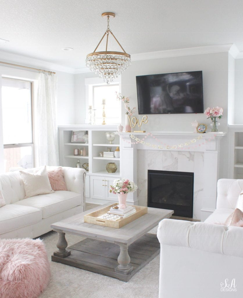 jeanette pink milk glass vase, blush pink valentine's day decor, crystorama chandelier, white and gold interiors, white interiors, classy interiors, television above mantel mantle, tv above fireplace, valentines banner garland, white chesterfield tufted sofa, vintage pink milkglass, pink faux fur ottoman pouf, coffee table styling, interior design style stylish books for coffee table, fresh flowers, blush pink faux fur pouf ottoman perigold