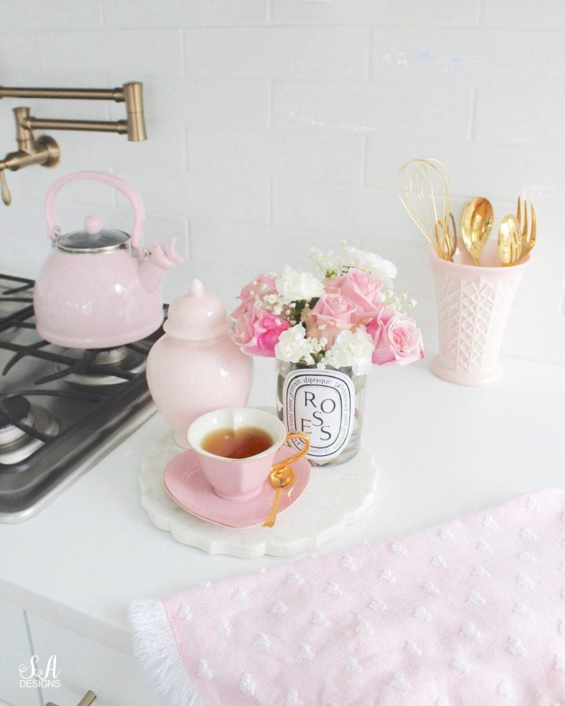 heart-shaped pink tea cup and saucer, diptyque candle with flowers, pink tea pot, gold brass bronze delta pot filler, pink milk glass vase, gold serve ware, marble tray, pink ginger jar, Starbucks copycat medicine ball recipe at home, Starbucks copycat citrus defender recipe at home