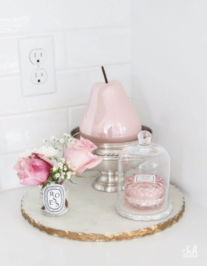 repurposed diptyque candle jar as vase with flowers, marble board, blush pink pear decoration in kitchen, pottery barn silver vintage pedestal bowl engraved dish, voluspa macaron rose candle with glass cloche dome