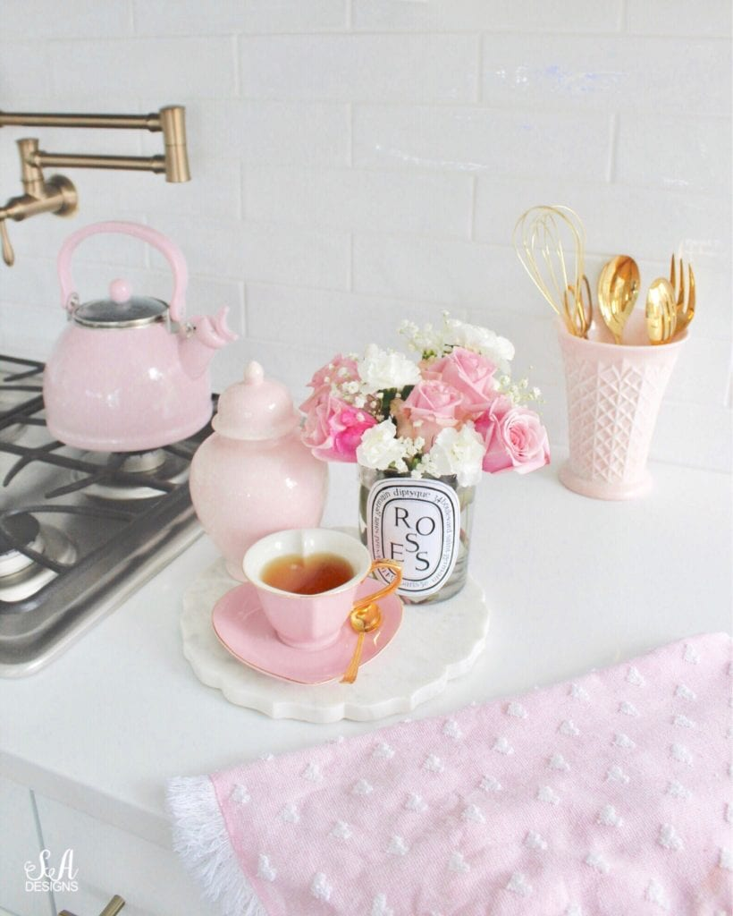 repurposed diptyque paris candles as vase with flowers, pink teapot, pink heart shaped teacup, pink milk glass, pink ginger jar, brass gold delta pot filler, heart kitchen towel, gold kitchen utensils, herbal tea