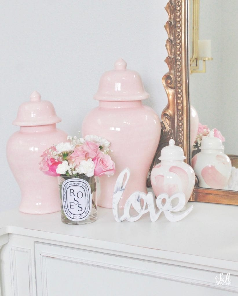 repurposed diptyque paris candles as vase with flowers, pink ginger jars, anthropologie gleaming primrose mirror, blush pink brush stroke ginger jar