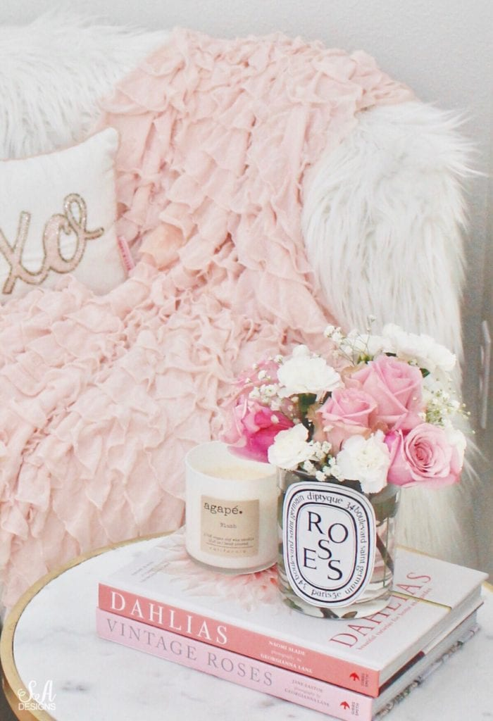 repurposed diptyque candle jar as vase with flowers, faux fur bench, shabby chic blush pink ruffle throw blanket, pink bow suede heels pumps, marble end table, Georgianna Lane Books Dahlias Peonies Roses, Agape Candles Blush