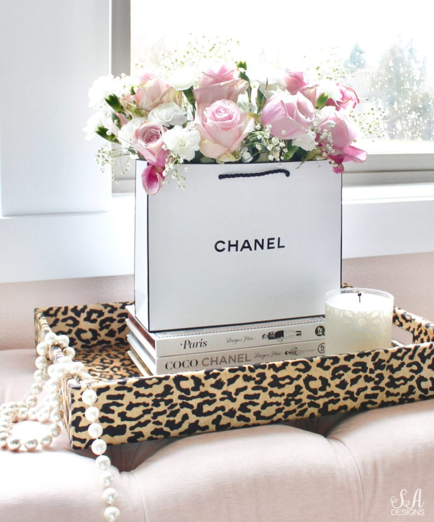chanel shopping bag with real fresh flowers, celine pink handbag, nude patent heels pumps, faux fur rug, blush pink tufted bench, real vintage pearls, leopard print tray, repurposed designer shopping bag, chanel bag, megan hess fashion books, megan hess paris, megan hess coco chanel book, megan hess new york book, tory burch candle