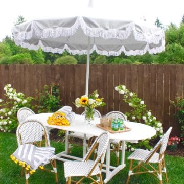 serena and lily fringed umbrella granite white, coastal decor, newport beach style, newport umbrella, hamptons style umbrella, grey and white umbrella with fringe, gray white umbrella fringe, garden outdoor party, gray white bistro chairs
