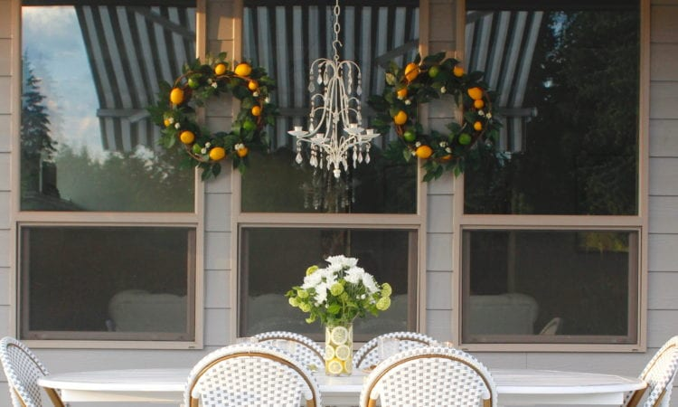 grey and white striped retractable awning, french outdoor patio, french style outdoor patio dining, french coastal backyard landscape dining outdoor design, english garden lemon tablescape, serena and lily outdoor umbrella, serena and lily grey white french bistro chairs, white oval outdoor dining patio table, outdoor patio table dining set, gold brass bar cart, lemon and fruit floral arrangement, outdoor patio chandelier, lemon tree