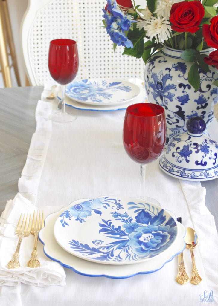 aerin plates williams-sonoma, scalloped blue rimmed plates, blue and white floral places,patriotic Tablescape, fourth of July table, red white and blue Tablescape table setting place setting, chinoiserie place setting, chinoiserie patriotic table, Aerin table place setting, Aerin plates Williams-Sonoma, scalloped plates, blue white plates, white ruffle dinner napkins, elegant gold flatware, red goblets, white ruffle table runners, white kitchen