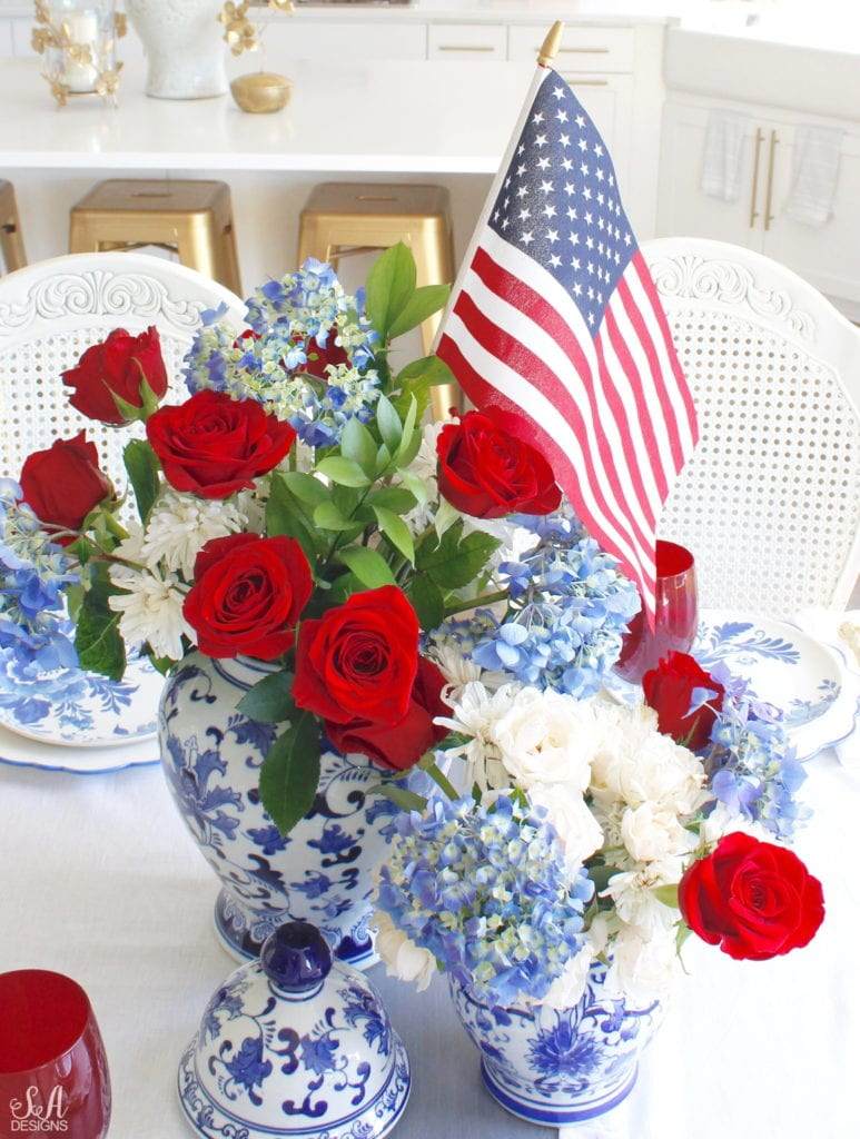 patriotic Tablescape, fourth of July table, red white and blue Tablescape table setting place setting, chinoiserie place setting, chinoiserie patriotic table, Aerin table place setting, Aerin plates Williams-Sonoma, scalloped plates, blue white plates, white ruffle dinner napkins, elegant gold flatware, red goblets, white ruffle table runners, white kitchen