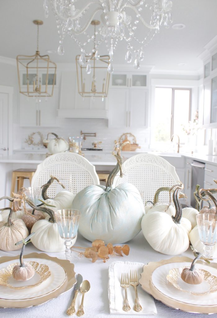 classy fall table, glam fall table, glam fall tablescape, elegant fall tablescape, white and gold fall table, gilded fall table, spa blue fall table, hot skwash velvet pumpkins, patina vie Aquarius goblets, ruffled tablecloth, ruffled ivory dinner napkins, gold flatware, gold-rimmed plates, gold flower butter plate dessert plates, vintage milk glass plates gold rim, gold chargers, pier1 gold eucalyptus stems, pier1 gold money glitter stems, white and gold fall kitchen decor, white velvet pumpkins, bellacor minka lavery pendants, white kitchen design, velvet pumpkins with Swarovski crystals, French country dining set, coastal kitchen, transitional kitchen, contemporary white elegant kitchen