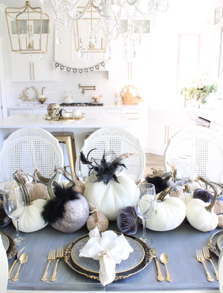 hot skwash velvet pumpkins, snakeskin print pumpkins, black Audrey Hepburn dress amazon fashion, halloween tablescape, halloween table, halloween table decor, elegant halloween decor, elegant halloween table, chic halloween table, Glam Halloween table, black and white halloween table, snakeskin halloween table decor, black and gold chargers, gold rimmed plates, gold flatware, black branch, gold rhinestone napkin rings, ivory white ruffle linen dinner napkins, black crows halloween decorations, white kitchen design, white and gold kitchen, white and brass kitchen