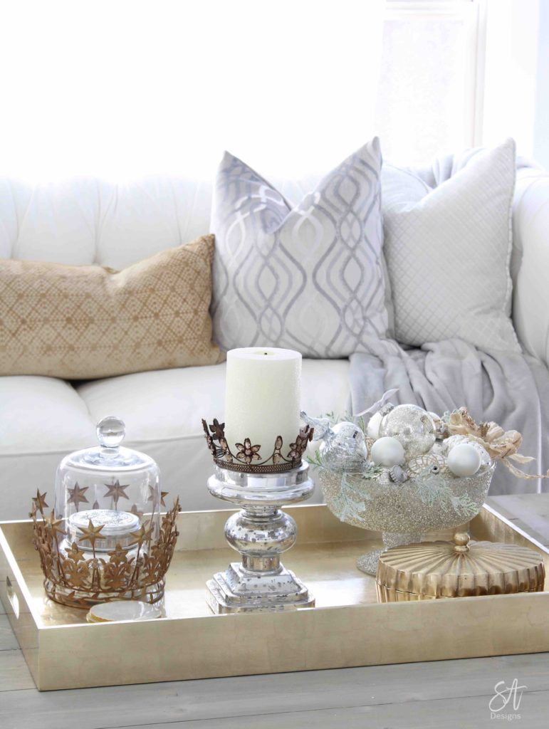 white and gold elegant glam Christmas decor, Christmas coffee table, ornaments in ZGallerie beaded pedestal bowl with ribbon, terrain Anthropologie Santos crowns, crowns on candlesticks, mercury glass candlesticks, Christmas coffee table, gold lacquer tray, restoration hardware baluster coffee table, grey and gold velvet pillows