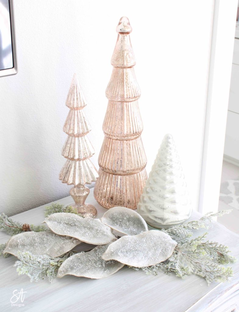 white Christmas tree, pink poinsettia Christmas ornaments, vintage pink glass ornaments, crown Christmas tree topper, romantic Christmas bedroom, blush pink mercury glass trees, glitter reindeer, blue pink velvet quilted bedding, blush pink fringe ottoman, pottery barn jewelry storage, Christmas bedroom decor ideas, master bedroom Christmas decorating ideas