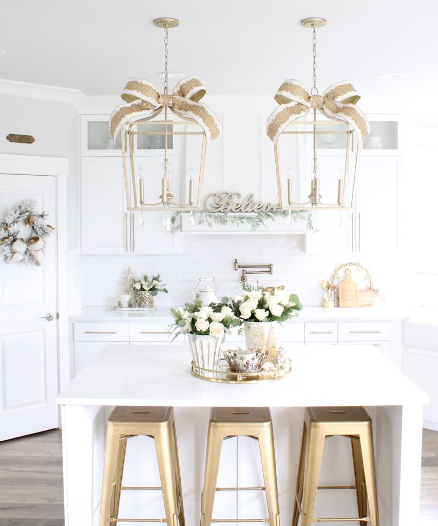 white and gold Christmas kitchen, glam Christmas kitchen, ribbon bows on kitchen pendants lighting, Christmas bows on kitchen lights, elegant Christmas kitchen, classy Christmas kitchen decorating, d. Stevens white and gold rhinestone Christmas ribbon, specialty white velvet gold rhinestone wired edge ribbon, gold barstools, Christmas floral arrangements, white and gold Christmas wreath, white kitchen design, white Christmas decor, white and gold Christmas kitchen decor