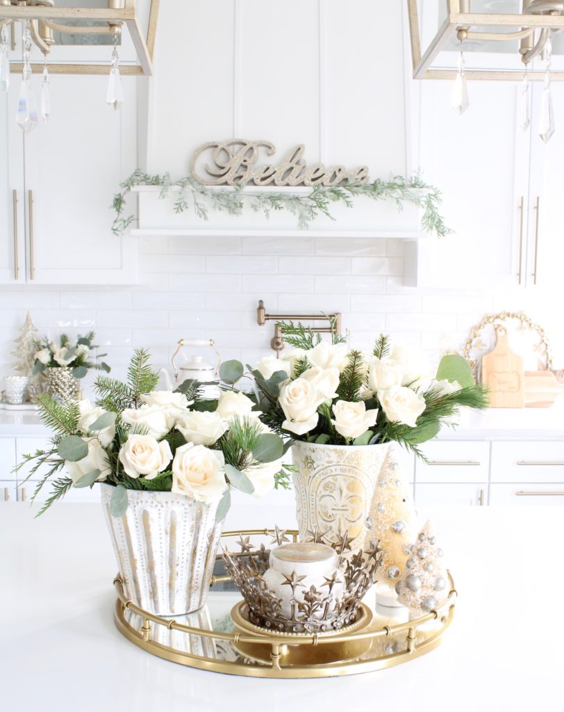 white and gold Christmas kitchen, glam Christmas kitchen, ribbon bows on kitchen pendants lighting, Christmas bows on kitchen lights, elegant Christmas kitchen, classy Christmas kitchen decorating, d. Stevens white and gold rhinestone Christmas ribbon, specialty white velvet gold rhinestone wired edge ribbon, gold barstools, Christmas floral arrangements, white and gold Christmas wreath, white kitchen design, white Christmas decor, white and gold Christmas kitchen decor, pottery barn mercury glass hurricanes