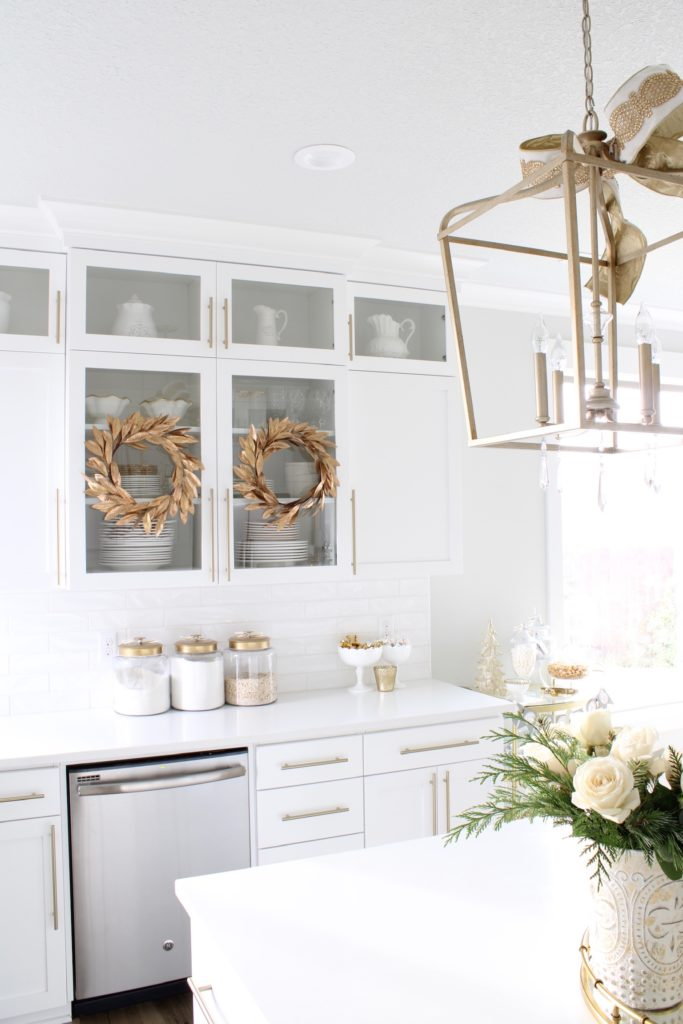 gold wreaths on white cabinets,white and gold Christmas kitchen, glam Christmas kitchen, ribbon bows on kitchen pendants lighting, Christmas bows on kitchen lights, elegant Christmas kitchen, classy Christmas kitchen decorating, d. Stevens white and gold rhinestone Christmas ribbon, specialty white velvet gold rhinestone wired edge ribbon, gold barstools, Christmas floral arrangements, white and gold Christmas wreath, white kitchen design, white Christmas decor, white and gold Christmas kitchen decor