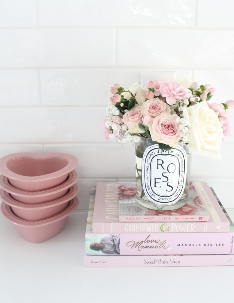 pink cookbooks, pink heart-shaped baking dishes, diptyque candles with flowers, pink macarons,Voluspa candles, Voluspa 123 oz rose candle, valentines diy fresh flowers arrangement at home, classy Valentine's Day decor, elegant Valentine's decor, soft romantic pink Valentine's Day decor, glam Valentine's decorations, classy elegant glam Valentine's pennant banner garland, Valentine's flower arrangements, pink ginger jars, Valentine's candy bar buffet, Valentine's cocoa hot chocolate bar, Valentine's bar cart, Valentine's living room decor, Valentine's entry way decor, classy glam elegant Valentine's Day decorating ideas, white kitchen decorated for Valentine's Day, elegant Valentine's tablescapes, gold mirrored tray, gold sequin heart banner, mercury glass votives pottery barn, ruffle cake stand, voluspa macaron candles, milk glass pedestal bowls