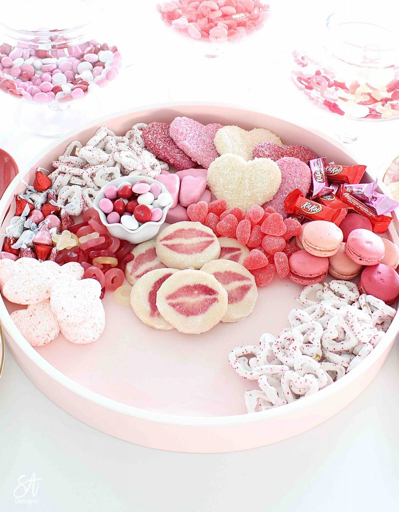 Valentine's Day dessert board, Valentine's Day charcuterie dessert board, dessert tray, dessert board, dessert candy board, dessert charcuterie board tray, pink circle round tray, pink candy dessert cookie tray, white kitchen entertaining, white kitchen island, white and gold decor, white and gold kitchen design, elegant glam white kitchen, white kitchen island, gold brass pendant kitchen lighting, Lindt chocolates, ghiradelli chocolates, Valentine's Day chocolate candies, dessert ideas, the prettiest dessert board ever, blogger dessert board, candy board tray, valentine's fashion, top knot pearl headband, voluspa candle, French pink Valentine's Day macarons, Reese's peanut butter hearts, Valentine's Day heart and lips cookies, Whole Foods market valentine's cookies