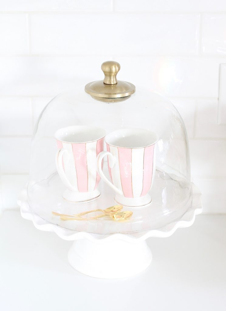 striped pink teacups stacked on white ruffle cake stand under cloche dome, pink and blue spring kitchen decor, white kitchen design, white and gold kitchen, voluspa large 5 wick candle, voluspa macaron candles, white hood, white and gold kitchen, kitchen goals, Caitlin Wilson blue bread cutting board French blue, blogger kitchen inspiration