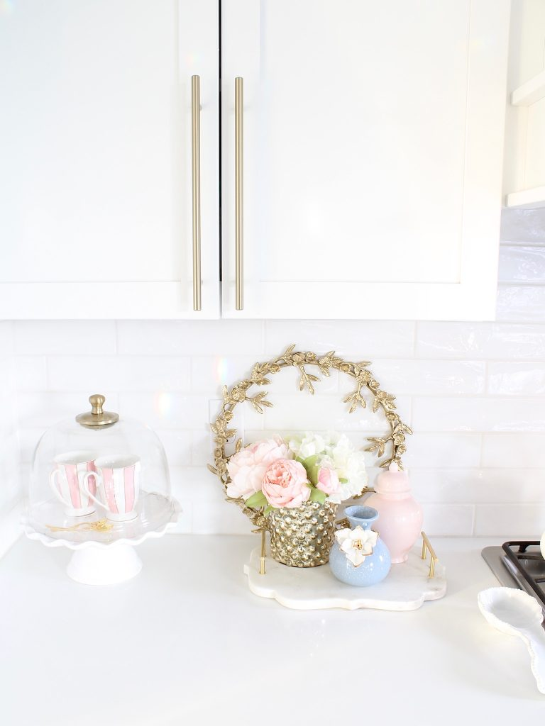 pink and blue spring kitchen decor, white kitchen design, white and gold kitchen, voluspa large 5 wick candle, voluspa macaron candles, white hood, white and gold kitchen, kitchen goals, Caitlin Wilson blue bread cutting board French blue, blogger kitchen inspiration