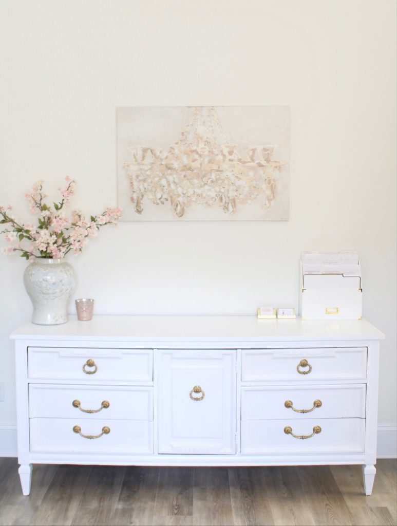 white and gold office, blush office, glam office, etagere gold shelves, Maltese dog, nesting boxes, home office, feminine office, diptyque candles used a flower vase, upcycled diptyque candle holder, white ginger jar pink cherry blossom stems, white matted gold frame set, office accessories, desk accessories, leopard slippers, white and gold leather office chair with wheels, pink pom pom throw blanket, blush tassel tote, gold office shelves, office shelving, how to decorate shelves, blogger office, Oliver gal candelabro canvas print