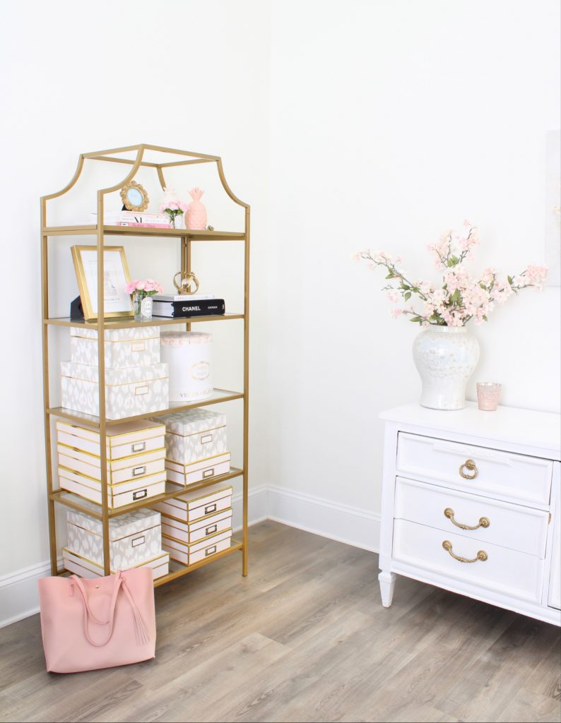white and gold office, blush office, glam office, etagere gold shelves, Maltese dog, nesting boxes, home office, feminine office, diptyque candles used a flower vase, upcycled diptyque candle holder, white ginger jar pink cherry blossom stems, white matted gold frame set, office accessories, desk accessories, leopard slippers, white and gold leather office chair with wheels, pink pom pom throw blanket, blush tassel tote, gold office shelves, office shelving, how to decorate shelves, blogger office
