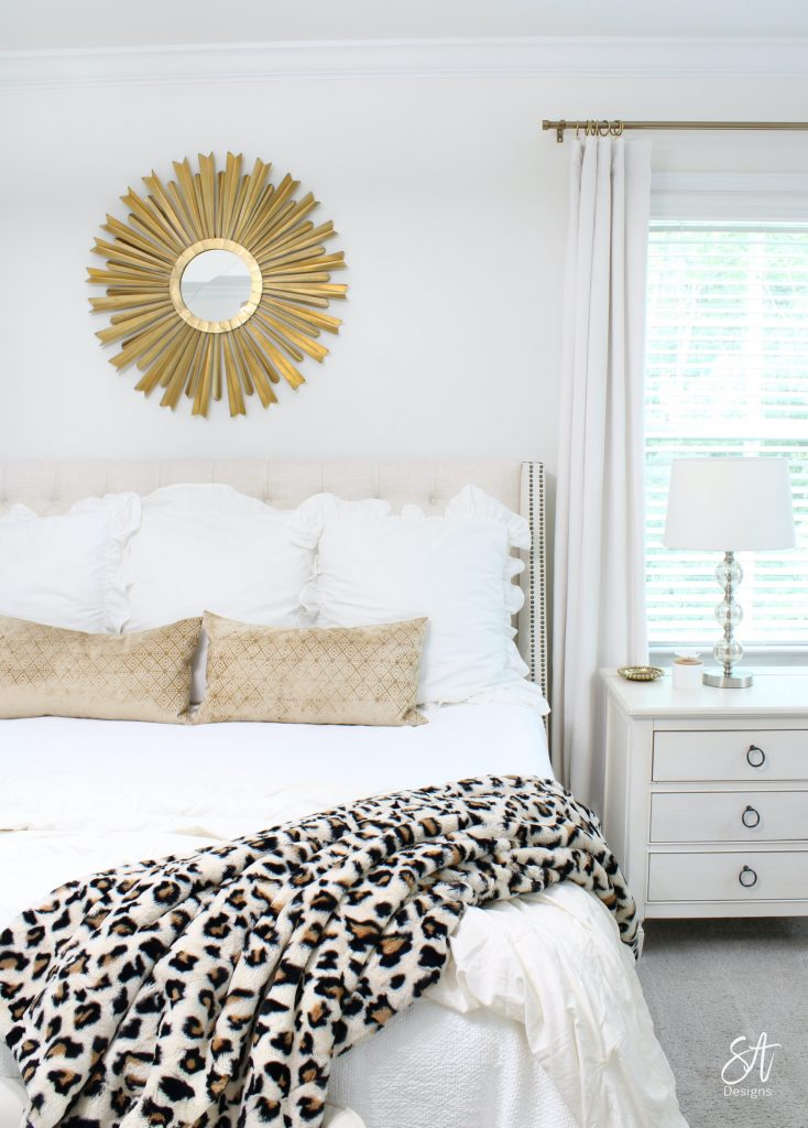 clear beaded gold glam chandelier, gold modern chandelier, black white gold modern transitional chic master bedroom, glam bedrooms, black and white bedrooms, bench for end of bed, glam venetian mirror, white and gold vanity, modern vanity bench, white and gold decor, leopard minky couture throw blanket, gold starburst sunburst wall mirror, perfect gold brass curtain rods, affordable window treatments, perfect white velvet curtains